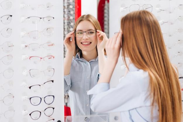 Glückliche frau, die nach neuen gläsern am optometriker sucht Kostenlose Fotos