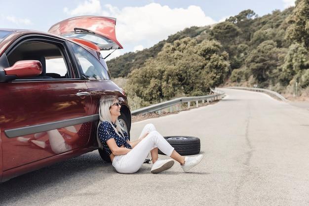 Glückliche frau, die nahe dem aufgegliederten auto auf kurvenreicher straße sitzt Kostenlose Fotos