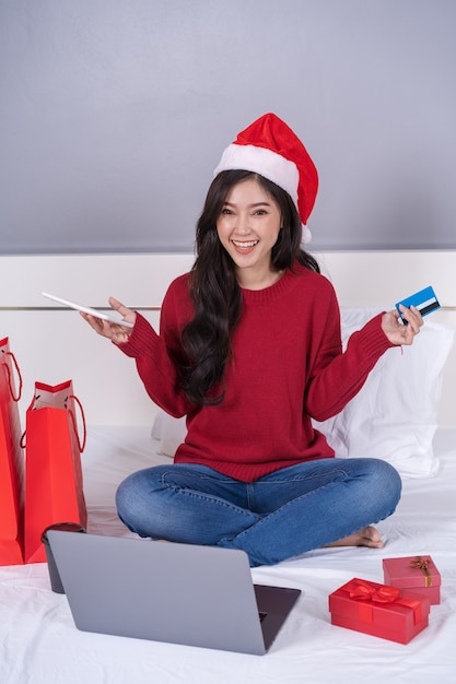 Glückliche frau, die online für weihnachtsgeschenk mit digitaler tablette und kreditkarte auf bett kauft Premium Fotos