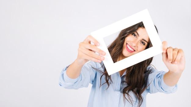 Glückliche frau, die rahmen vor gesicht hält Kostenlose Fotos