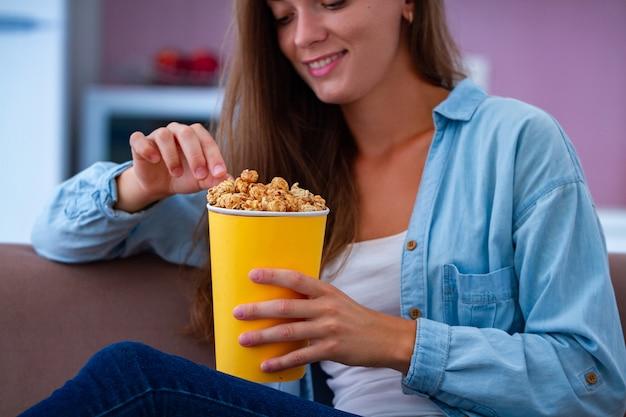 Glückliche frau, die ruhendes und knuspriges karamellpopcorn beim fernsehen zu hause ausruht und isst. popcorn-film Premium Fotos