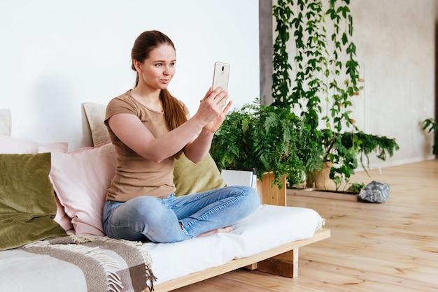 Glückliche frau, die smartphone für videoanruffreunde und -eltern verwendet, lächelndes mädchen, das zu hause auf sofa spaßgruß online durch webcam sitzt, der videoanruf macht Premium Fotos