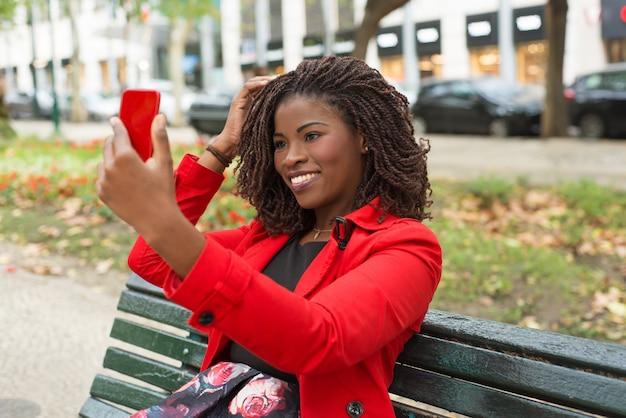 Glückliche frau, die smartphone im park verwendet Kostenlose Fotos