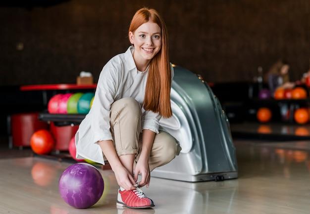 Glückliche frau, die spitzee in einem bowlingspielverein bindet Kostenlose Fotos