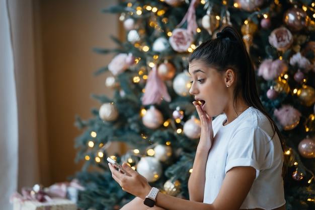 Glückliche frau, die videoanruf mit ihrer familie oder freunden hat. junge frau verwendet eine digitale tafel nahe geschmücktem festlichem baum zu hause. Kostenlose Fotos
