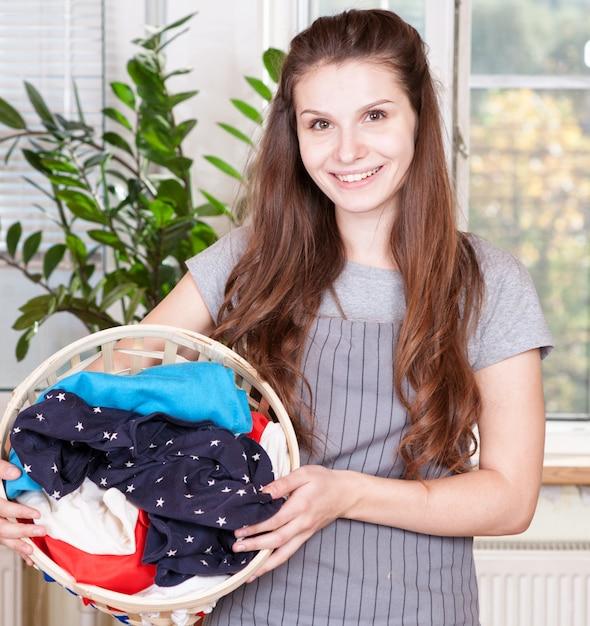 Glückliche frau, die wäschekorb im küchenraum trägt Premium Fotos