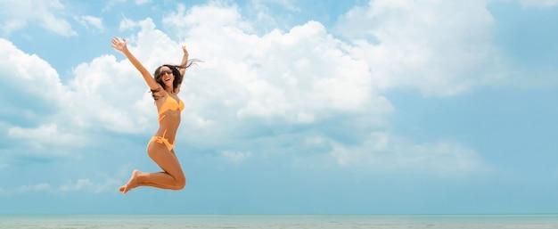 Glückliche frau im bikini, der am strand im sommer springt Premium Fotos