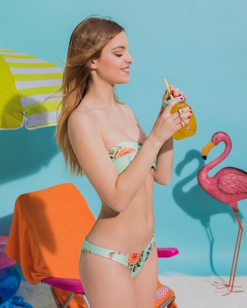 Glückliche frau im bikini, der cocktail hält Kostenlose Fotos