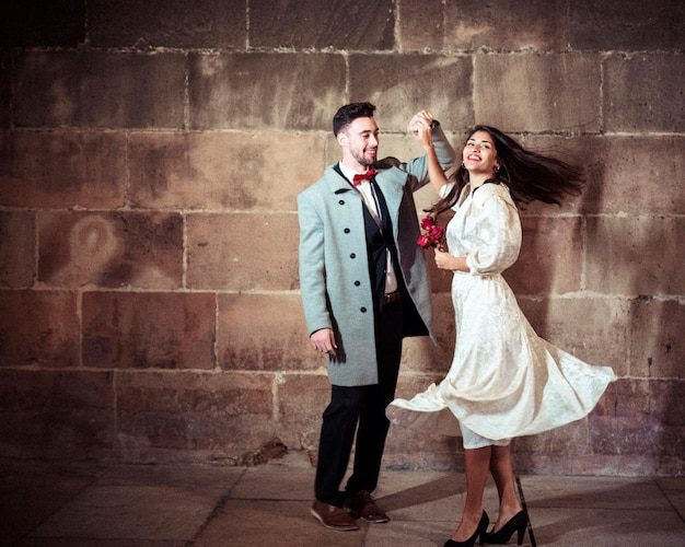 Glückliche frau im kleid, das mit mann in der straße tanzt Kostenlose Fotos
