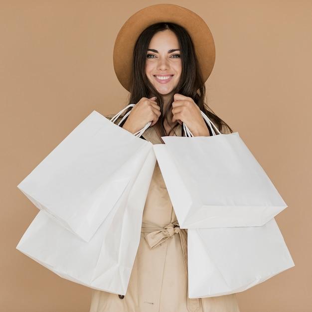 Glückliche frau im mantel mit vielen einkaufsnetzen Kostenlose Fotos