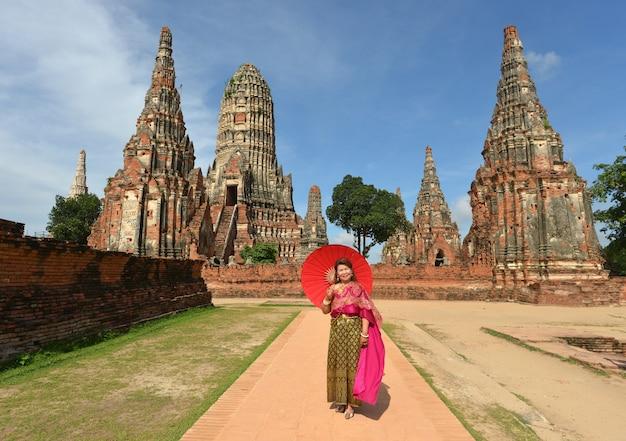 Glückliche frau im ruhestand in der traditionellen thailändischen kleiderreise am tempel. Kostenlose Fotos