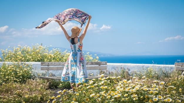 Glückliche frau im schönen kleid mit blumen. feld mit gänseblümchen. Premium Fotos