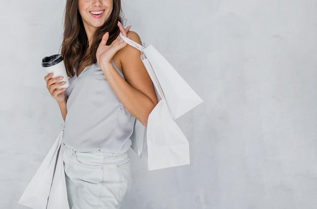 Glückliche frau im unterhemd mit einkaufsnetzen und kaffee Kostenlose Fotos