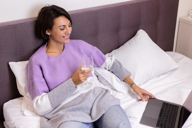 Glückliche frau im warmen pullover im bett mit glas wein