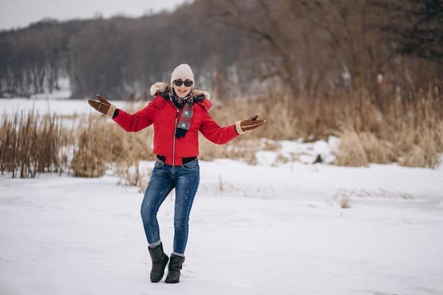 Glückliche frau in der roten jacke draußen im winter Kostenlose Fotos