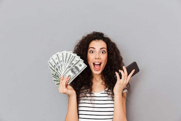 Glückliche frau mit dem gelockten haar, das fan von 100 dollarscheinen und von smartphone in den händen zeigen, dass sie unter verwendung des elektronischen geräts viel geld verdienen können Kostenlose Fotos