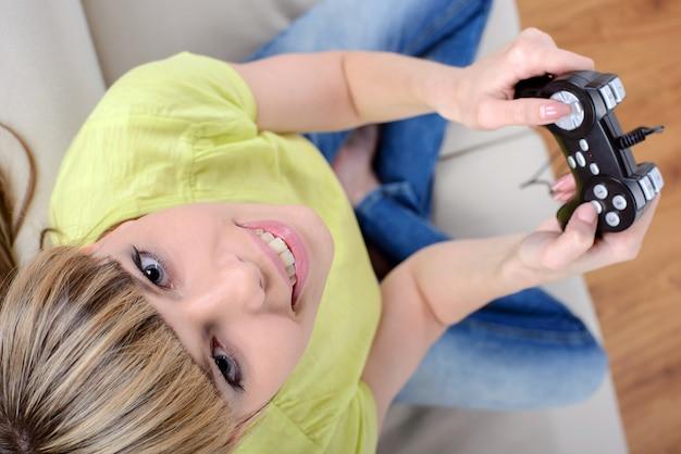 Glückliche frau mit dem steuerknüppel, der videospiele spielt. Premium Fotos
