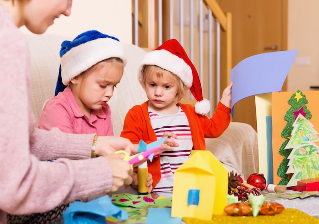 Glückliche frau mit den mädchen, die für weihnachten sich vorbereiten Premium Fotos