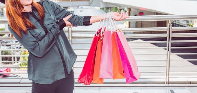 Glückliche frau mit einkaufstüten beim einkaufen genießen. frauen einkaufen, lifestyle-konzept Premium Fotos