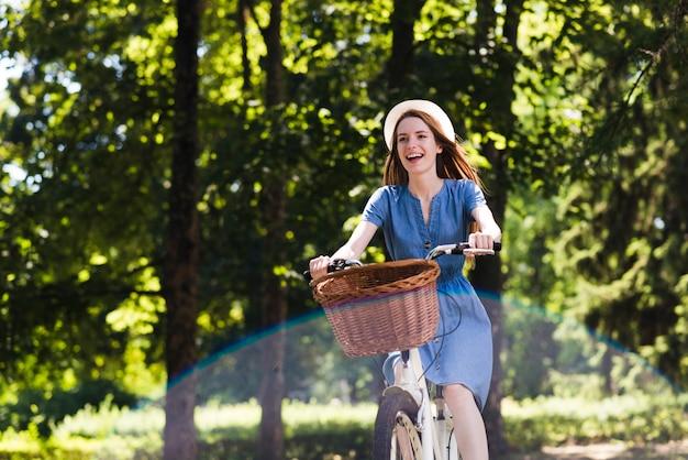 Glückliche frau mit fahrrad im wald Kostenlose Fotos