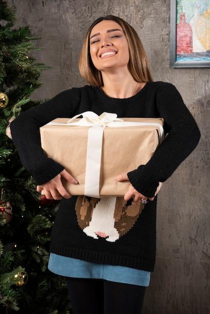 Glückliche frau mit geschlossenen augen, die ein weihnachtsgeschenk halten. hochwertiges foto Kostenlose Fotos