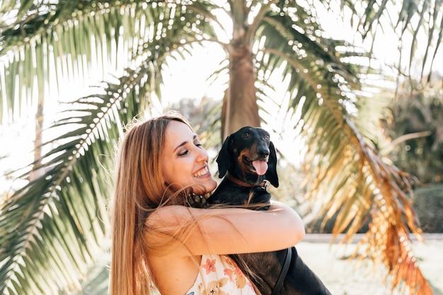 Glückliche frau mit ihrem hund, der heraus zunge haftet Kostenlose Fotos