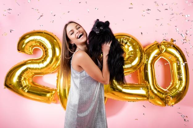 Glückliche frau mit japanischem spitzschwarzhund und konfettis und goldenen 2020 ballonen des neuen jahres lokalisiert über rosa Premium Fotos