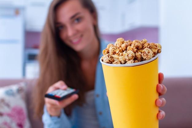 Glückliche frau mit knusprigem karamell-popcorn-kasten beim ansehen des films zu hause Premium Fotos