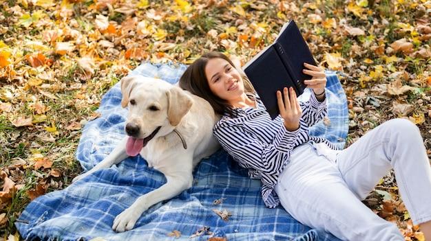Glückliche frau mit labrador im park Kostenlose Fotos