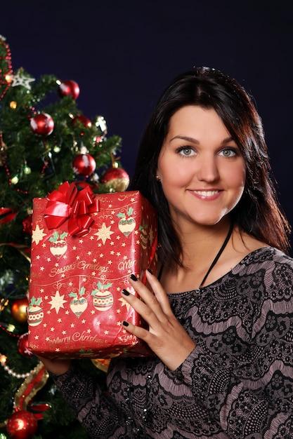 Glückliche frau mit weihnachtsgeschenk Kostenlose Fotos