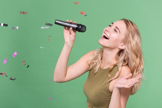 Glückliche frau singt, umgeben von konfetti Premium Fotos
