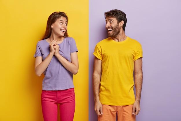 Glückliche frau und mann schauen sich fröhlich an, gekleidet in lebendige sommerkleidung, viel spaß Kostenlose Fotos