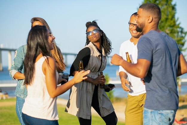 Glückliche frauen und männer, die in park am abend tanzen. freundliche freunde, die mit bier während des sonnenuntergangs sich entspannen. freizeit-konzept Kostenlose Fotos