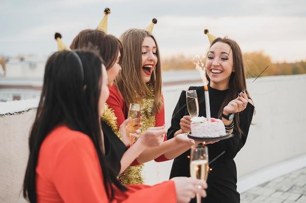 Glückliche frauengruppe, die den geburtstag auf der dachspitze feiert Kostenlose Fotos