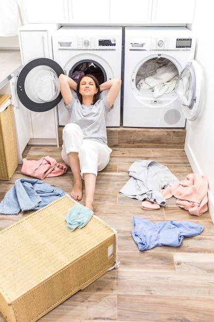Glückliche frauenhausfrau in der waschküche nahe der waschmaschine mit schmutziger kleidung Premium Fotos