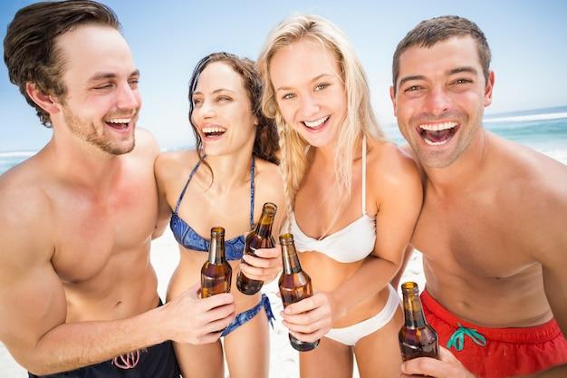 Glückliche freunde am strand genießen Premium Fotos
