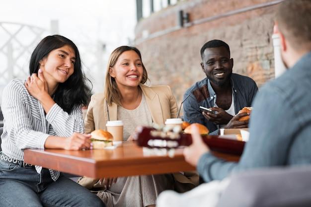 Glückliche freunde am tisch mit burgern Kostenlose Fotos