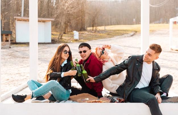 Glückliche freunde auf picknick bier klirren Kostenlose Fotos