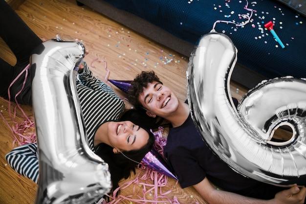 Glückliche freunde des hohen winkels, die ballone lachen und halten Kostenlose Fotos