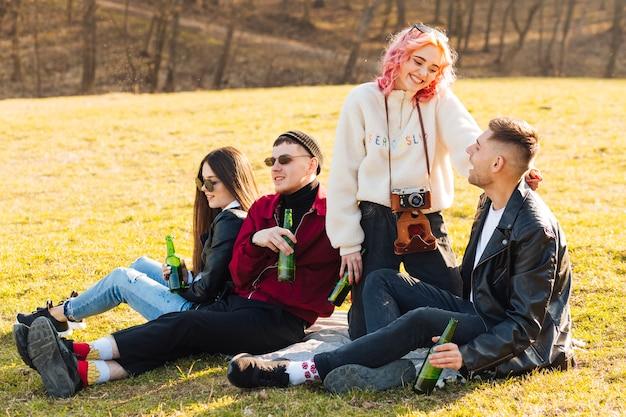 Glückliche freunde, die auf gras sitzen und picknick mit bier haben Kostenlose Fotos