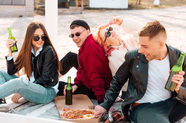 Glückliche freunde, die die party sitzen auf dem boden haben Kostenlose Fotos
