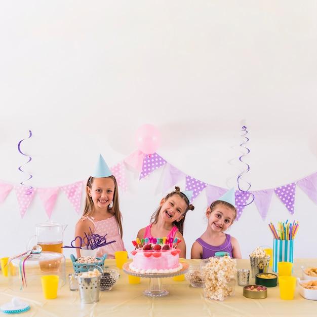 Glückliche freunde, die geburtstagsfeier mit geschmackvollem snack und kuchen auf tabelle genießen Kostenlose Fotos