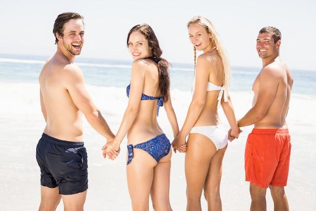 Glückliche freunde, die hände am strand zusammenhalten Premium Fotos