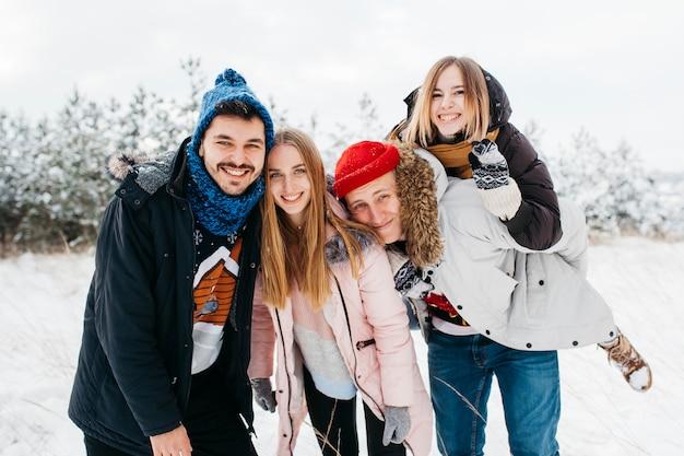 Glückliche freunde, die im winterwald stehen Kostenlose Fotos
