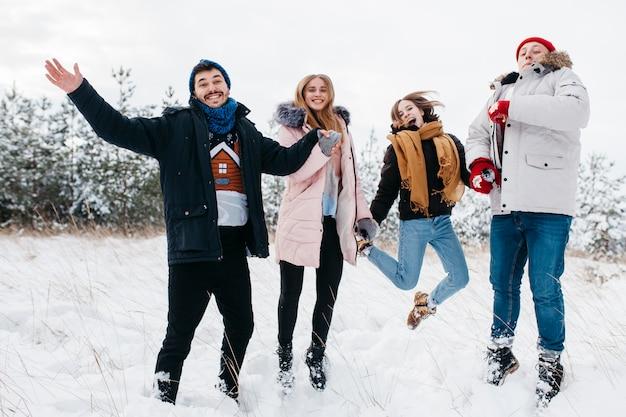 Glückliche freunde, die in winterwald springen Kostenlose Fotos