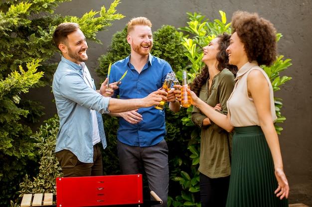 Glückliche freunde, die lebensmittel grillen und draußen grillparty genießen Premium Fotos