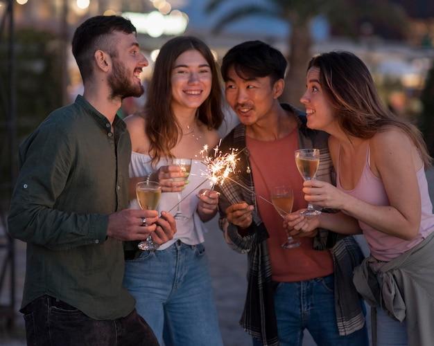 Glückliche freunde, die mit feuerwerk feiern Kostenlose Fotos