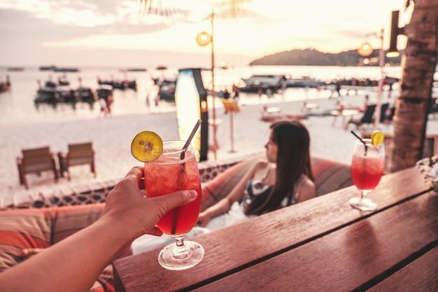 Glückliche freunde, die mit tropischen cocktails auf der strandparty zujubeln Premium Fotos