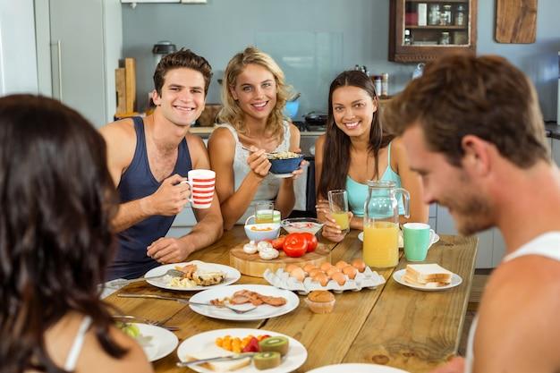 Glückliche freunde, die paare beim frühstücken schauen Premium Fotos