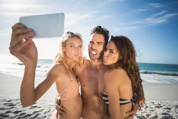 Glückliche freunde, die selfie am strand nehmen Premium Fotos